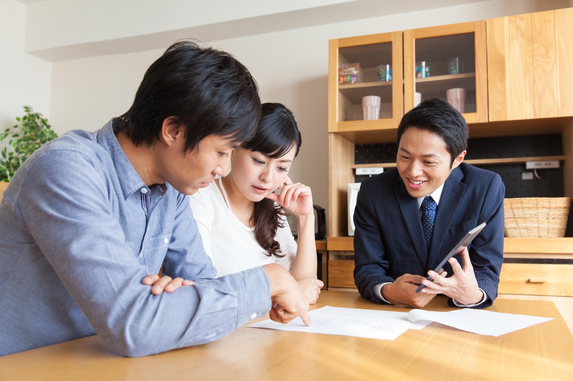 契約の書面を交わす不用品回収業者と依頼者夫妻。