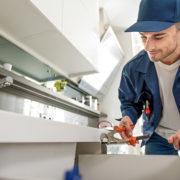 笑顔で水道修理をする男性