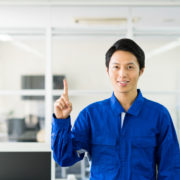 作業服で指を指している男性。