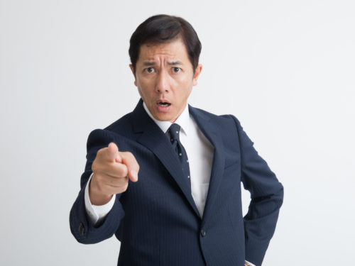 怒った顔で指を差すスーツの男性