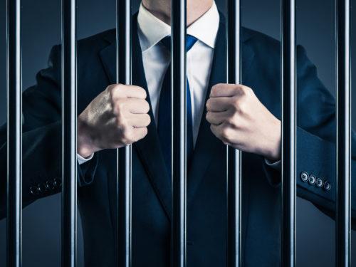 牢屋の中のスーツの男性