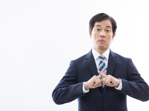 指でバツを作るスーツの男性