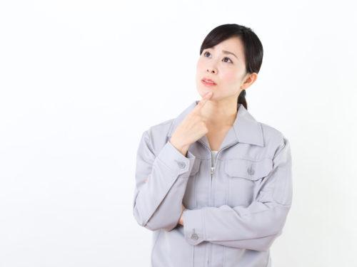 悩んでいる作業服の女性